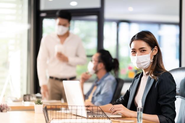 Portret van aziatische kantoor werknemer zakenvrouw dragen beschermend gezichtsmasker werken in nieuw normaal kantoor met interraciale collega. praktijk op sociale afstand voorkomt coronavirus covid-19.