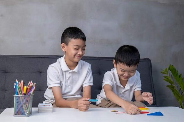 Portret van aziatische kinderen die kleurrijke blokken spelen, leren door het thuisschoolconcept van het onderwijs te spelen, kinderen spelen met puzzel die tangram doet, onderwijsconcept, twee kinderen spelen met blokkenspellen.