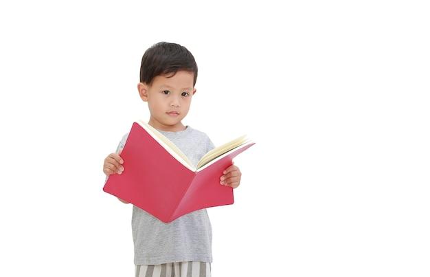 Portret van aziatische kleine babyjongen van ongeveer 3 jaar oud opent een boek op een witte geïsoleerde achtergrond met uitknippad. onderwijs concept