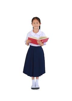 Portret van aziatische kleine schoolmeisje in thaise schooluniform staande met open tekstboek geïsoleerd op een witte achtergrond. volledige lengte met uitknippad.