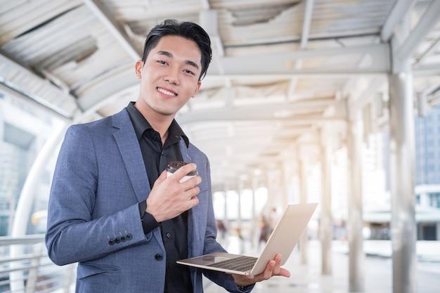 Portret van aziatische laptop van de zakenmanholding en koffiekop in de stad van het de bouwbureau