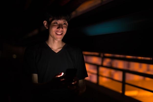 Portret van aziatische man buiten 's nachts op parkeerplaats met behulp van mob
