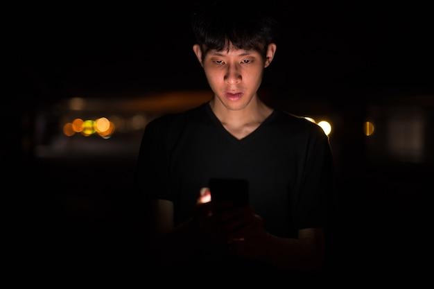 Portret van aziatische man buiten 's nachts op parkeerplaats met behulp van mob Premium Foto