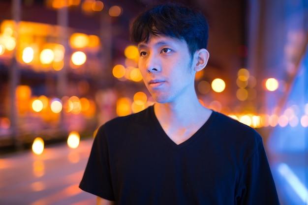 Portret van aziatische man denken buiten 's nachts