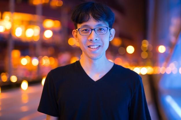 Portret van aziatische man die lacht buiten 's nachts