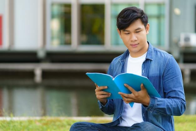 Portret van aziatische man universitaire student zittend op het gras in de campus