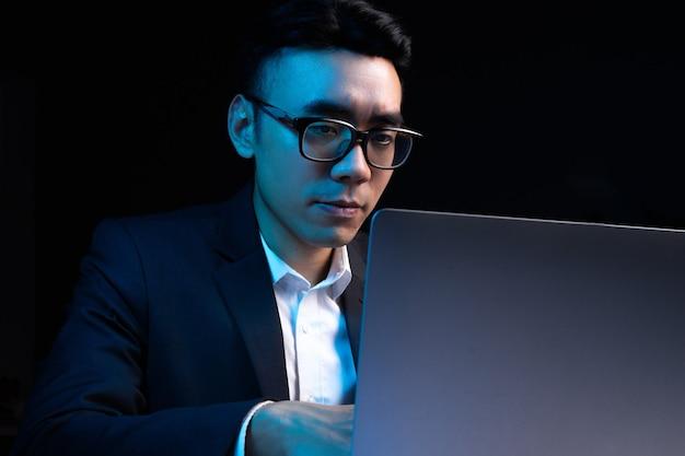 Portret van aziatische mannelijke programmeur die 's nachts werkt