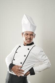 Portret van aziatische mensenchef-kok die rugpijn over wit geïsoleerde achtergrond voelen