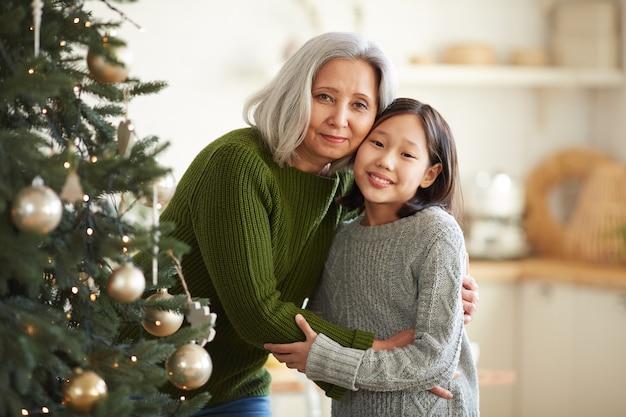 Portret van aziatische moeder die haar dochter omhelst die zich dichtbij de kerstboom bevindt die zij glimlachen