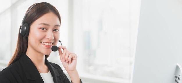 Portret van aziatische mooie glimlachende de telefoonexploitant van de vrouwenklantenondersteuning in bureau.