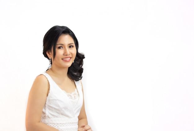 Portret van aziatische mooie lange zwarte haarvrouw die bij camera tegen witte achtergrond glimlacht