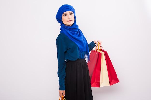 Portret van aziatische moslimvrouw met boodschappentassen op witte achtergrond.
