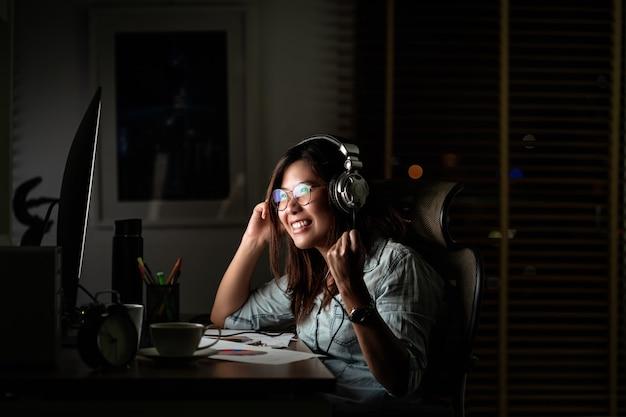 Portret van aziatische onderneemster die de muziek via hoofdtelefoon en slimme mobiele telefoon luistert