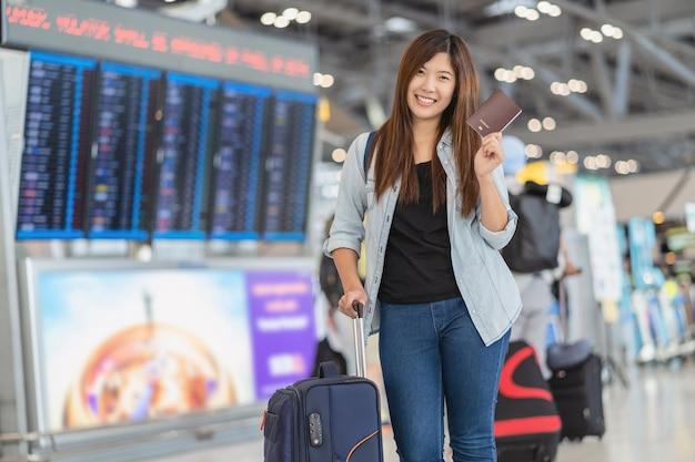 Portret van aziatische reiziger met bagage met paspoort die boven het vluchtbord staat