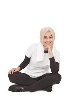 Portret van aziatische sportieve vrouw die lacht zittend op de vloer