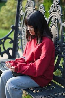 Portret van aziatische tiener die oogglazen draagt die op bank zitten