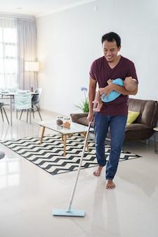 Portret van aziatische vader die de vloer schoonmaakt met behulp van een bezem terwijl hij zijn baby draagt