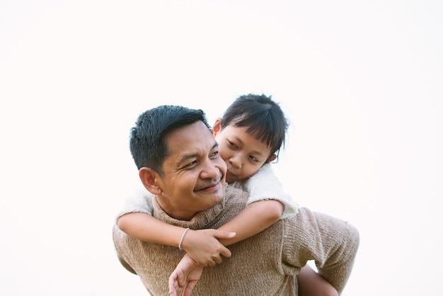 Portret van aziatische vader die zijn dochter op zijn rug vervoert
