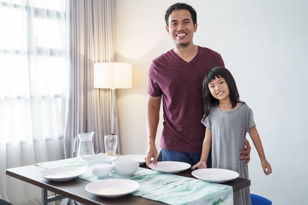 Portret van aziatische vader en kleine dochter eettafel voorbereiden op het diner