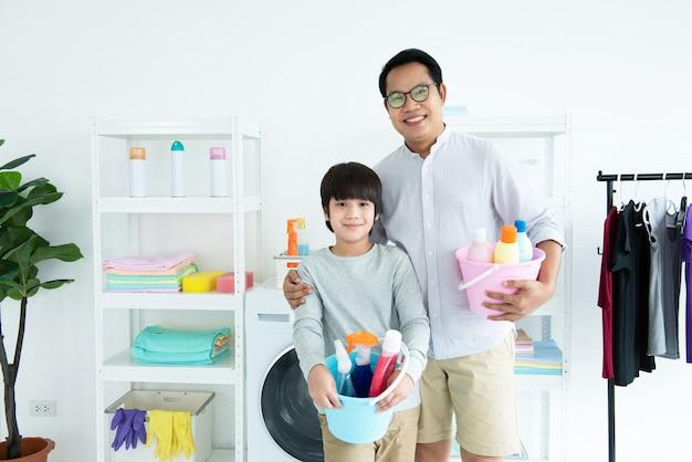 Portret van aziatische vader en zoonhandgreep die huishoudelijke apparaten schoonmaken.