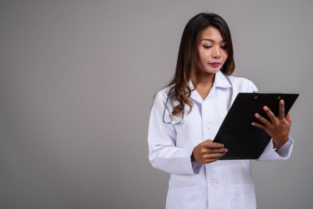 Portret van aziatische vrouw arts klembord houden