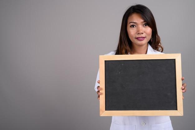 Portret van aziatische vrouw arts met bord