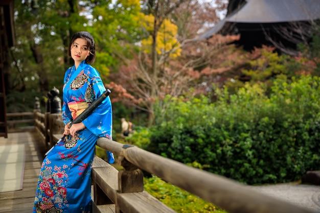 Portret van aziatische vrouw die de blauwe kimono en paraplu van japan op holdingshand draagt