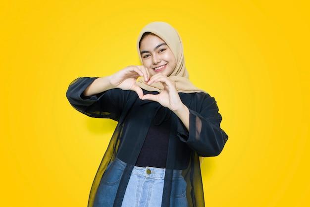 Portret van aziatische vrouw die de vorm van het hartsymbool met handen op gele muur doen