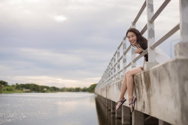 Portret van aziatische vrouw die in openlucht dichtbij de rivier lacht; gelukkig wijfje dat over rivier glimlacht.