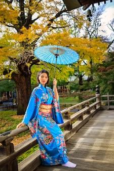 Portret van aziatische vrouw die japanse blauwe kimono en paraplu op holdingshand draagt