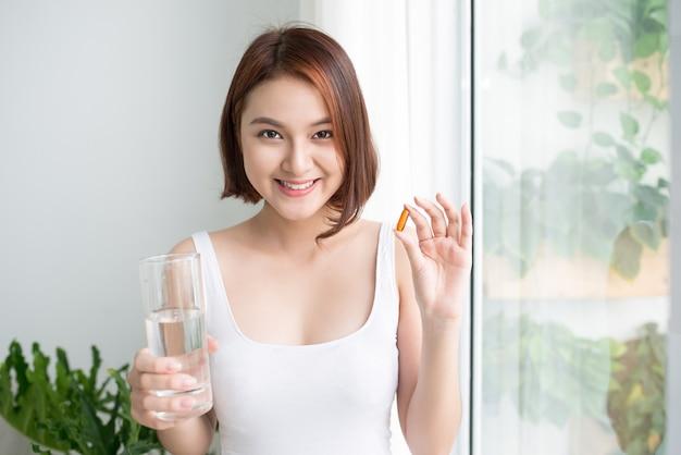 Portret van aziatische vrouw die omega 3 visoliecapsule thuis toont.