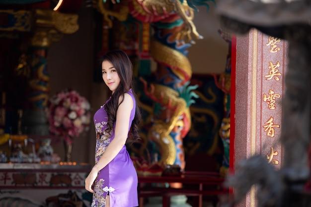 Portret van aziatische vrouw die purpere cheongsam dragen bij chinese tempel, chinees nieuwjaarfestival.