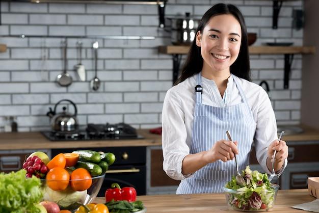 Portret van aziatische vrouw die salade in keuken mengt