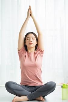 Portret van aziatische vrouw die thuis yoga beoefent