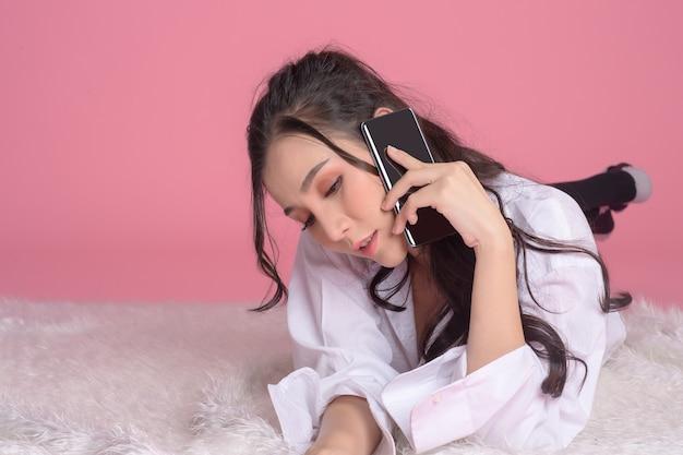 Portret van aziatische vrouw die wit overhemd draagt ?? gebruik van de smartphone die op bed op roze ligt.
