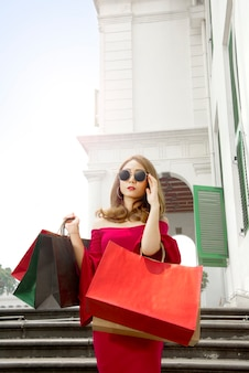 Portret van aziatische vrouw die zonnebril met het winkelen zakken draagt