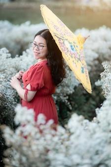 Portret van aziatische vrouw gelukkige reiziger met rode jurk houden gele paraplu genieten in wit bloeiend of witte margarita bloemenveld in de tuin van in chiang mai, thailand, reizen ontspannen vakantie