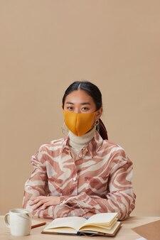 Portret van aziatische vrouw in beschermend masker voorzijde kijken terwijl zittend aan de tafel en studeren