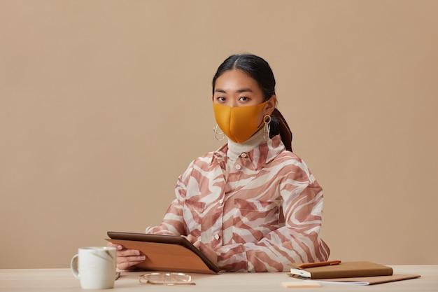Portret van aziatische vrouw in beschermend masker voorzijde kijken zittend aan tafel en met behulp van digitale tablet
