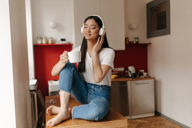 Portret van aziatische vrouw in denim broek en witte top ontspannen in koptelefoon met kopje koffie in de keuken