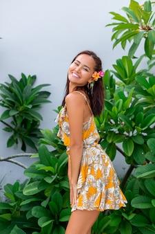 Portret van aziatische vrouw in gele zomerjurk staat met plumeria thaise bloem in haar en ronde oorbellen