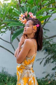 Portret van aziatische vrouw in gele zomerjurk staat met thaise bloem van plumeria in haar en ronde oorbellen.vrouw met lichte make-up buiten op de achtergrond van de muur en groene struiken