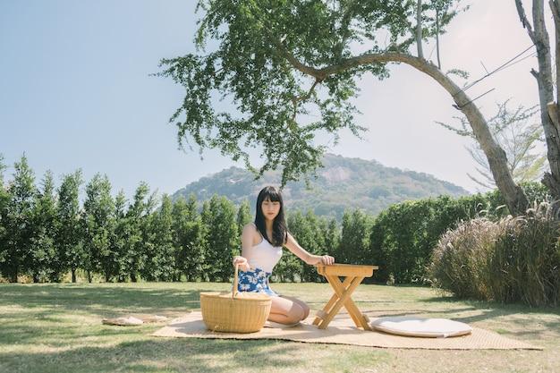 Portret van aziatische vrouw met mand zittend op een mat in park.