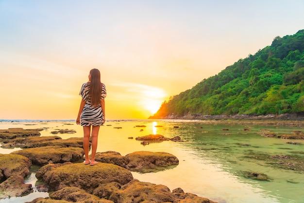 Portret van aziatische vrouw op de rots bij zonsondergang rond oceaan in vakantie