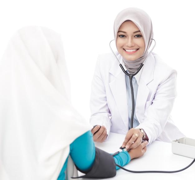 Portret van aziatische vrouwelijke arts die bloeddruk van een patiënt controleert die camera bekijkt