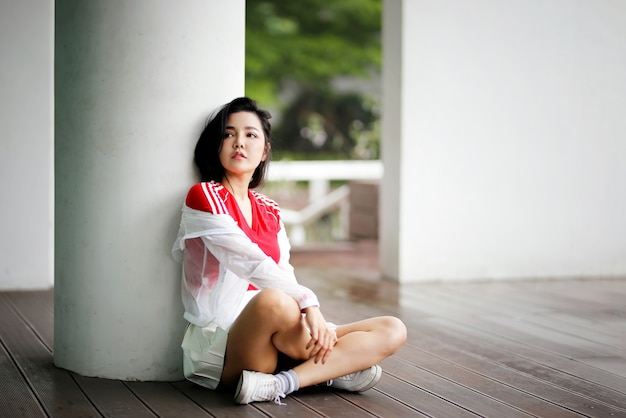 Portret van aziatische vrouwen kijken weg zittend buiten.