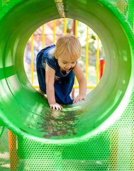 Portret van baby 1-2 jaar oud. gelukkig kaukasisch kindmeisje het spelen speelgoed bij de speelplaats. meisje lacht. kinderen en sport concept.