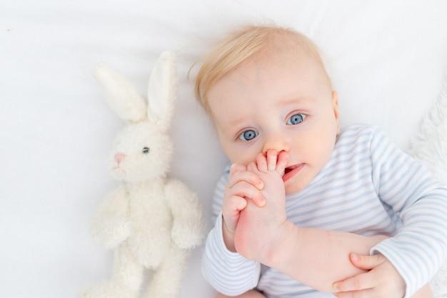 Portret van baby zuigen voet liggend op bed, baby jongen blonde zes maanden