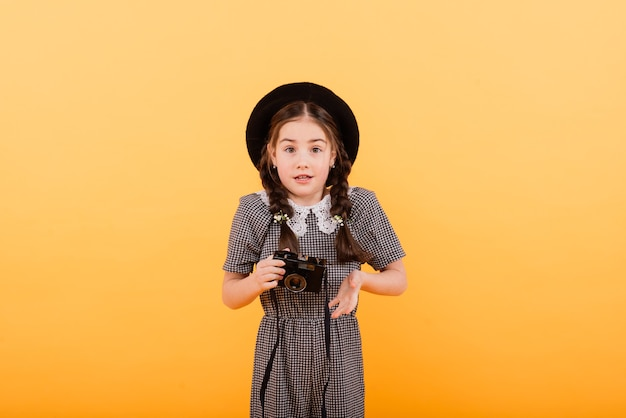 Portret van babymeisje met fotocamera geïsoleerd op een gele achtergrond