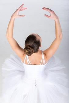 Portret van ballerina in klassieke tutu in de grijze studio.